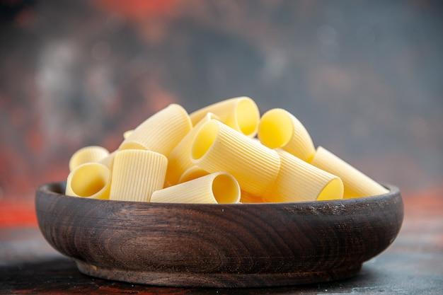 Bovenaanzicht van ongekookte pasta's in een bruine kom op een donkere achtergrond