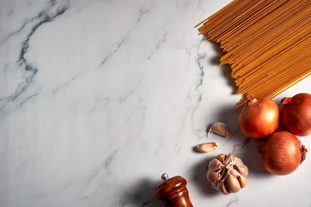 Bovenaanzicht van ongekookte pasta, ui en knoflook op een wit marmeren oppervlak