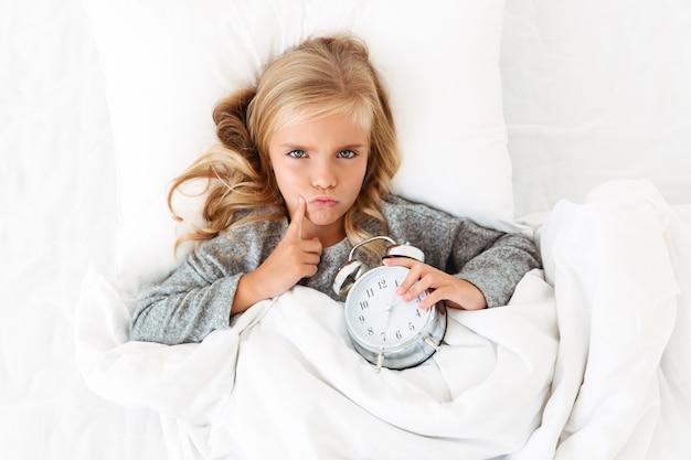 Bovenaanzicht van ongelukkig denkend meisje dat haar gezicht met vinger aanraakt terwijl het in bed met wekker ligt,