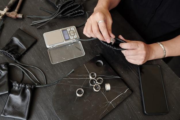 Bovenaanzicht van onherkenbare juwelier zittend aan tafel en verpakkingsring in leren tas voor cutomer