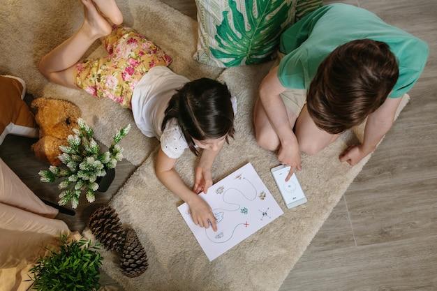 Bovenaanzicht van onherkenbare kinderen die thuis op het tapijt op schattenjacht spelen