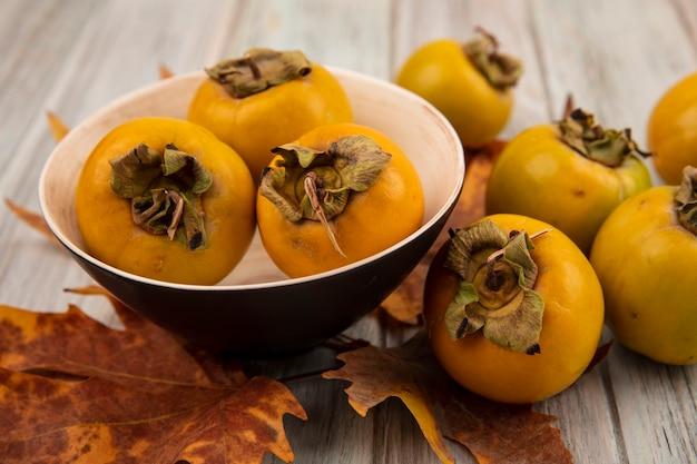 Bovenaanzicht van onrijpe kaki fruit op een kom met bladeren op een grijze houten tafel
