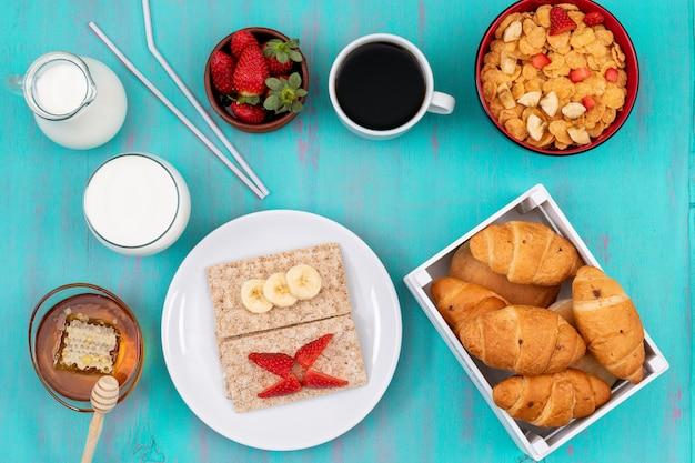 Bovenaanzicht van ontbijt met croissants, cornflakes, fruit, melk en honing op blauwe horizontale oppervlak