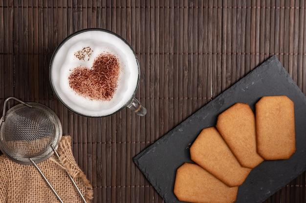 Bovenaanzicht van ontbijt met koekjes en koffie met een hart