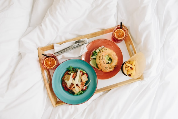 Bovenaanzicht van ontbijt of lunch in bed van een panzanella salade met croutons en een bagel met verse sla, twee drankjes en frietjes op een dienblad in kleurrijke borden
