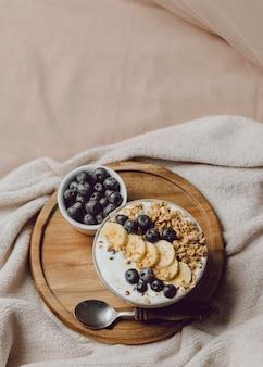 Bovenaanzicht van ontbijt op bed met granen en banaan