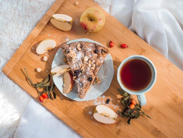 Bovenaanzicht van ontbijt op bed met lekkere taart en t op houten dienblad romantische ochtend op vakantie