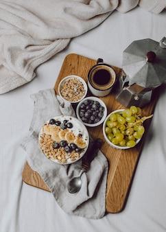 Bovenaanzicht van ontbijt op bed met ontbijtgranen en koffie