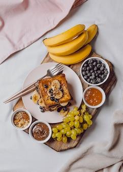 Bovenaanzicht van ontbijt op bed met toast en banaan