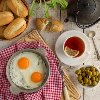 Bovenaanzicht van ontbijt opstelling met eieren, olijven, brood en zwarte thee