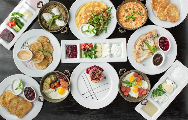 Bovenaanzicht van ontbijt setup met omelet, pannenkoeken, jam, toast, worst gerecht