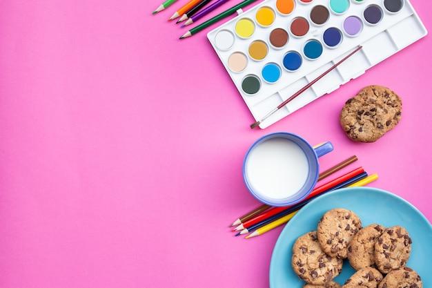 Bovenaanzicht van ontbijt van kleuren en aquarellen, met koekjes en melk met roze achtergrond en kopieerruimte aan de linkerkant