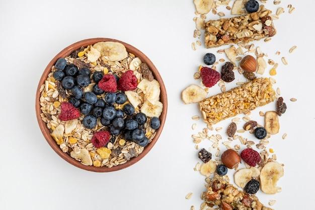 Bovenaanzicht van ontbijtgranenrepen met fruit en kom