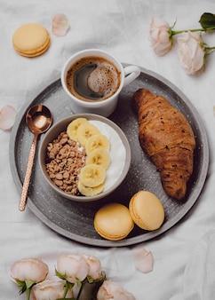 Bovenaanzicht van ontbijtkom met ontbijtgranen en croissants