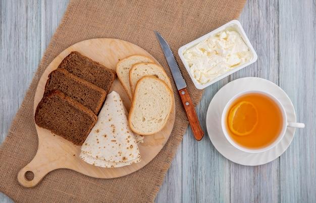 Bovenaanzicht van ontbijtset met brood als gesneden rogge witte en flatbread op snijplank met mes en clotted cream op zak en kopje hete grog op houten achtergrond