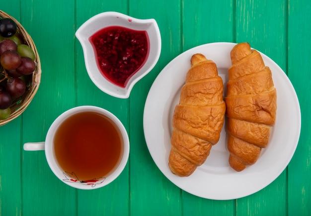 Bovenaanzicht van ontbijtset met croissants in plaat kopje thee frambozenjam in kom en mandje met druiven sleedoorn bessen op groene achtergrond
