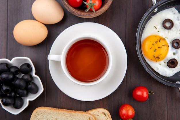 Bovenaanzicht van ontbijtset met kopje thee op schotel gebakken ei zwarte olijven brood sneetjes eieren en tomaten op hout