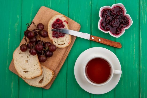 Bovenaanzicht van ontbijtset met sneetjes brood en druivenmost met mes en kopje thee met kom frambozenjam op groene achtergrond