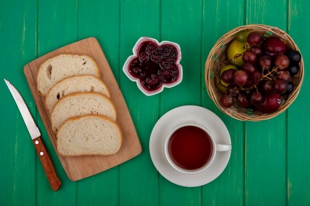 Bovenaanzicht van ontbijtset met sneetjes brood op snijplank frambozenjam en kopje thee met pluot en druivenmost in mand en mes op groene achtergrond