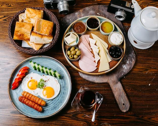 Bovenaanzicht van ontbijttafel met gebakken ei en worst verse groenten, kaas en ham