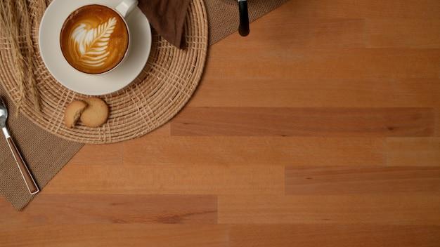 Bovenaanzicht van ontbijttafel met koffie en koekjes op placemat, servet en kopie ruimte