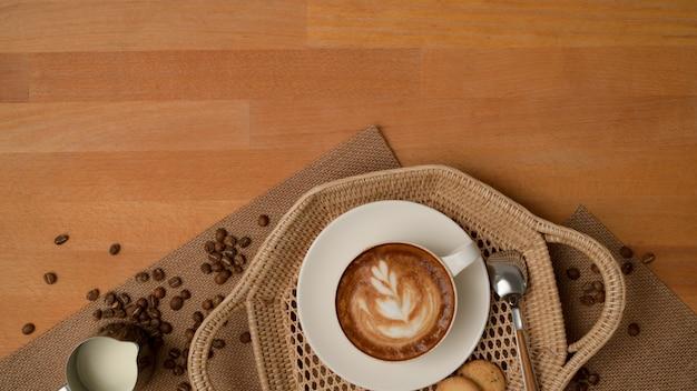 Bovenaanzicht van ontbijttafel met latte koffiekopje en koekjes op dienblad versierd met koffiebonen en placemat