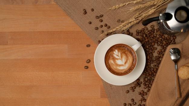 Bovenaanzicht van ontbijttafel met latte koffiekopje, koffiepot op placemat versierd met koffiebonen