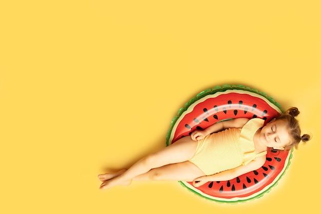 Bovenaanzicht van ontspannen kind in een zwembroek liggend op opblaasbare zwemmen gekleurde ring op gele muur