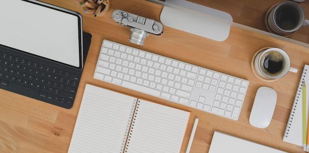 Bovenaanzicht van ontwerper werkplek met tablet, lege notebook kantoorbenodigdheden op houten tafel