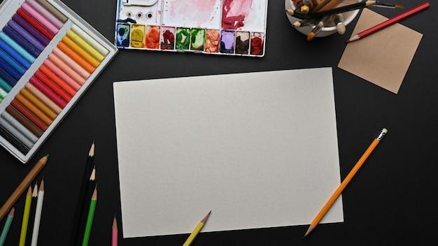 Bovenaanzicht van ontwerper werkruimte met blanco papier potloden en tekengereedschappen op tafel