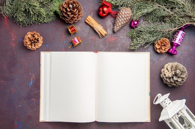 Bovenaanzicht van open beurt met kerstboom en kegels op zwart
