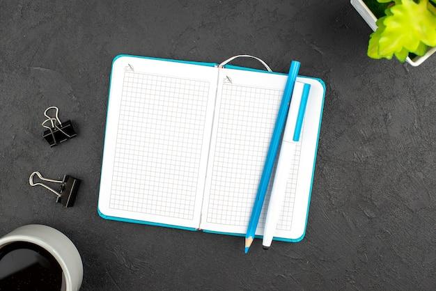 Bovenaanzicht van open blauw notitieboekje en pen een kopje met koffiebloempot op zwart