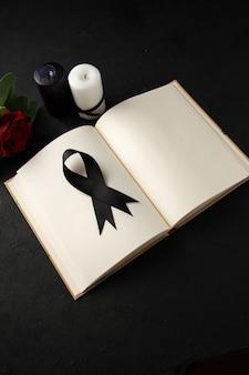 Bovenaanzicht van open boek met zwarte rouwboog op donkere muur