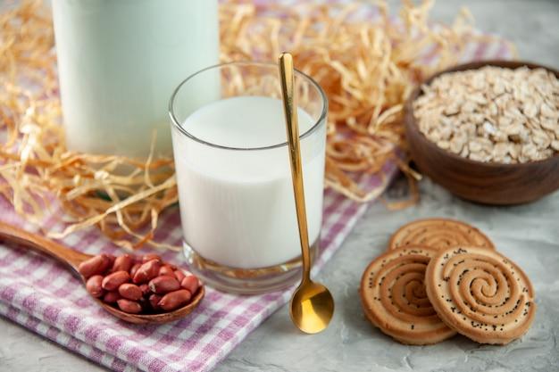Bovenaanzicht van open glazen beker gevuld met melk en bonen in lepelkoekjes haver op paarse gestripte handdoek