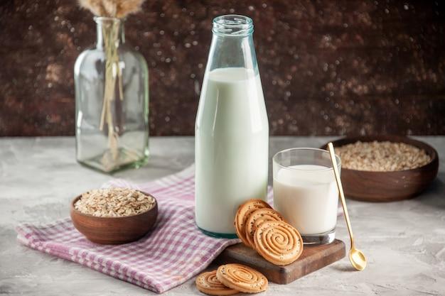 Bovenaanzicht van open glazen fles en beker gevuld met melkkoekjes, haver in bruine pot op paarse gestripte handdoek op houten snijplank