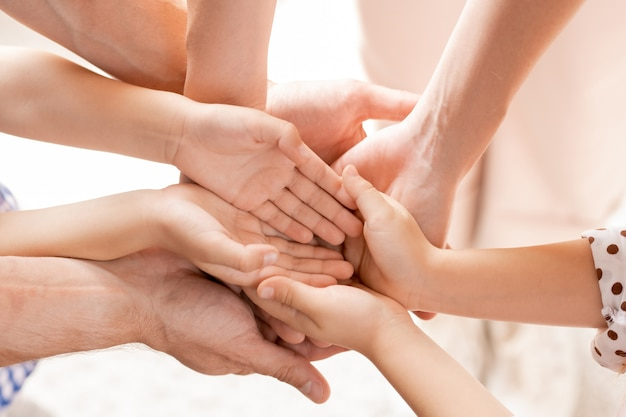 Bovenaanzicht van open handen van kleine kinderen en hun jonge ouders stapel maken als symbool van saamhorigheid, liefde en genegenheid
