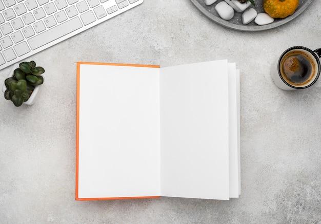 Bovenaanzicht van open hardcover boek op bureau met koffie