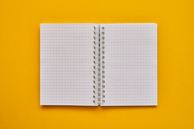 Bovenaanzicht van open laptop met blanco pagina's. schoolnotitieboekje op een gele achtergrond, spiraalvormig blocnote