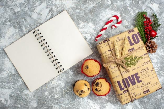 Bovenaanzicht van open notitieboekje en mooi verpakt kerstcadeau met liefdesinscriptie kleine cupcakes en sparren takken decoratie accessoires conifer kegel op ijs oppervlak