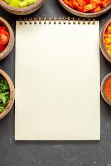 Bovenaanzicht van open notitieboekje en verschillende kruiden