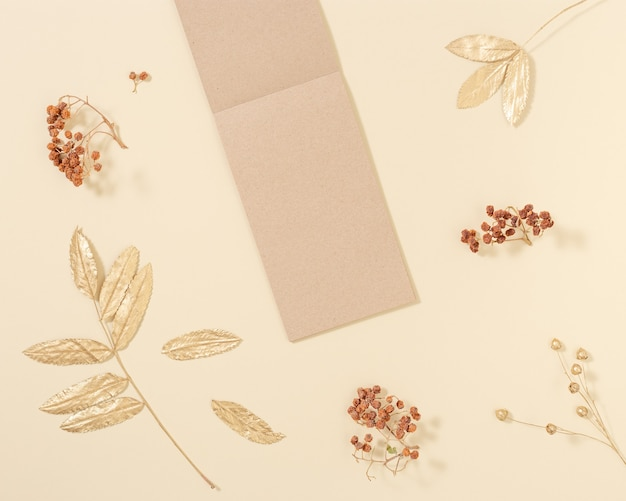 Bovenaanzicht van open notitieboekje met blanco pagina's van ambachtelijk papier voor het schrijven van notities met goud en neutrale herfstbladeren