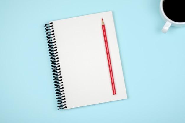 Bovenaanzicht van open spiraal leeg notitieblok op kleurrijke bureau