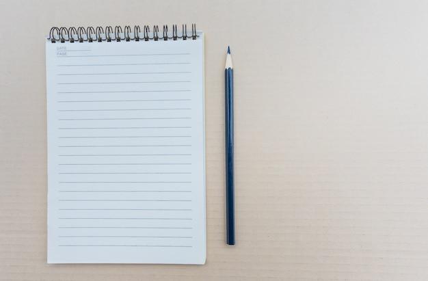 Bovenaanzicht van open spiraal leeg notitieboekje met potlood op bruine achtergrond.