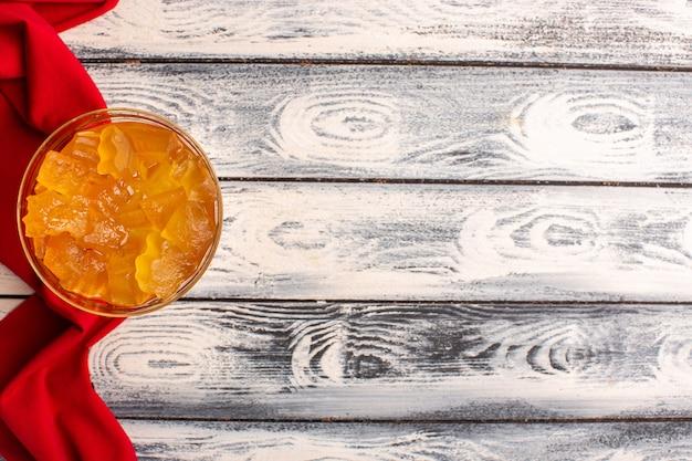 Bovenaanzicht van oranje gelei in glas op het grijze oppervlak