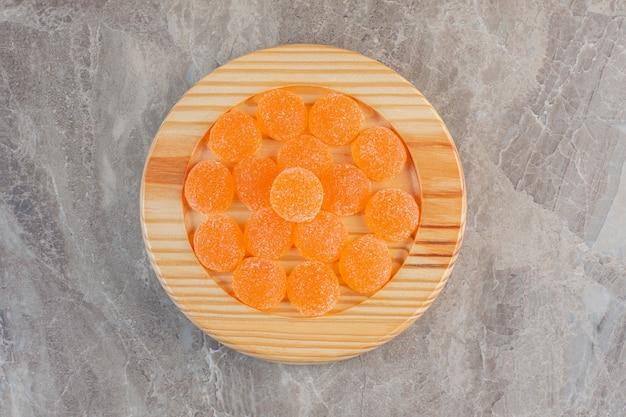 Bovenaanzicht van oranje gelei snoepjes op een houten bord.