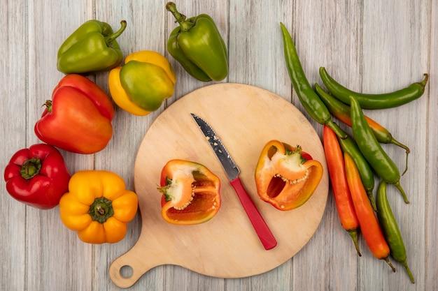 Bovenaanzicht van oranje halve paprika op een houten keukenbord met mes met kleurrijke paprika's geïsoleerd op een grijze houten achtergrond