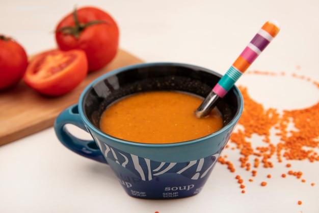 Bovenaanzicht van oranje linzensoep op een kom met lepel met tomaten op een houten keukenbord op een wit oppervlak