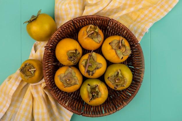 Bovenaanzicht van oranje onrijpe kaki fruit op een emmer op een geel geruit doek op een blauwe houten tafel