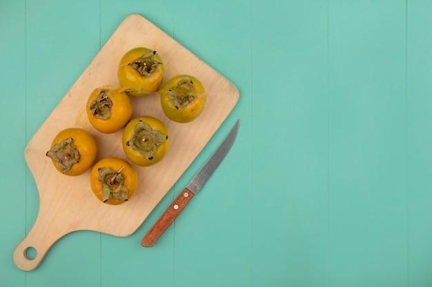 Bovenaanzicht van oranje onrijpe kaki fruit op een houten keukenplank met mes op een blauwe houten tafel met kopie ruimte