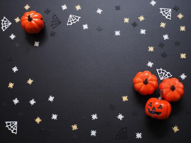 Bovenaanzicht van oranje pompoen, witte spinnen en gele webvorm op zwart, plat leggen